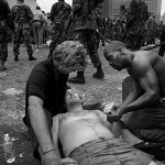 National Guard units turn their backs as civilians try to help a wounded man as they wait with thousands of other refugees for evacuation from the Superdome Thursday afternoon. 9/1/05